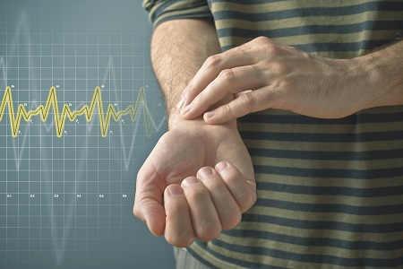 Man checking his pulse by pressing the wrist with fingers. Health issues concept.