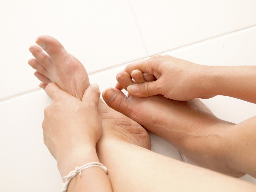 Female hands giving massage to bare foot