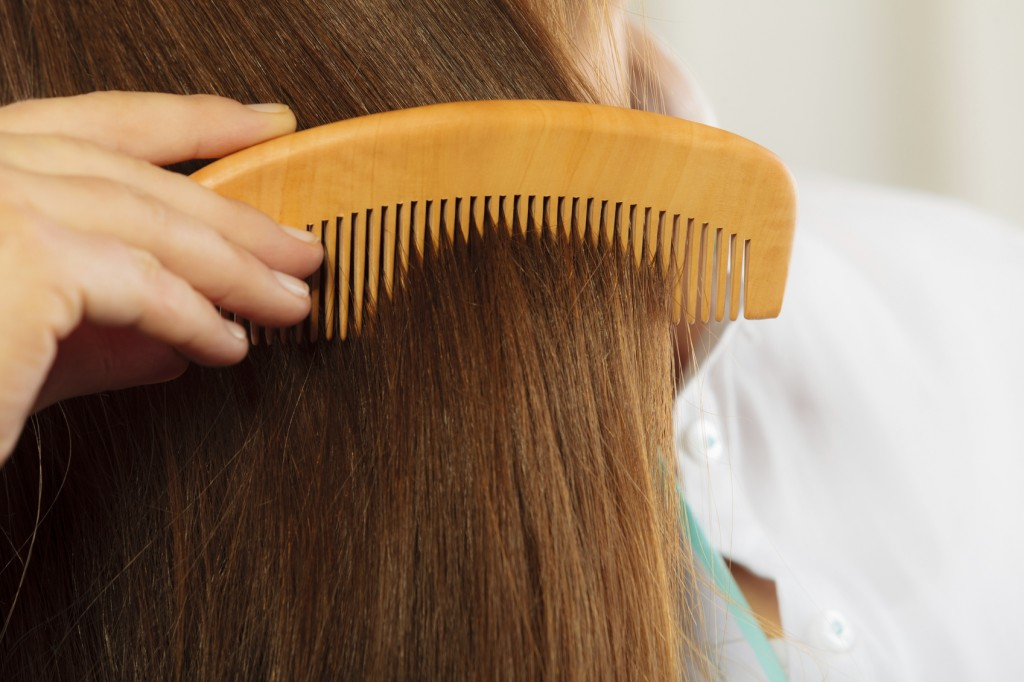 Closeup hair and hand with comb